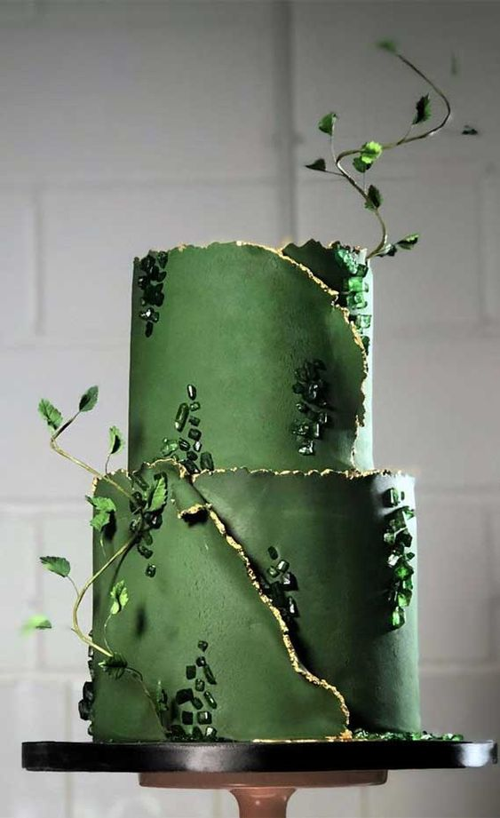 a grass green wedding cake with wrapping tiers, greenery branches and green rhinestones is a very beautiful and glam idea