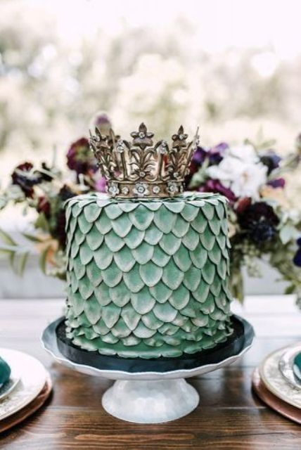 a green wedding cake reminding a dragon egg and topped with a crown for a Game Of Thrones wedding