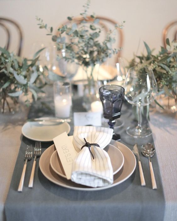 a grey and neutral wedding table with silver eucalyptus, candles, grey table runners, plates and glasses looks peaceful and stylish