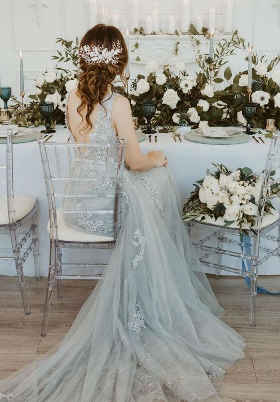 a grey lace A-line wedding dress with no sleeves, cutout back and a train for a very refined winter bridal look