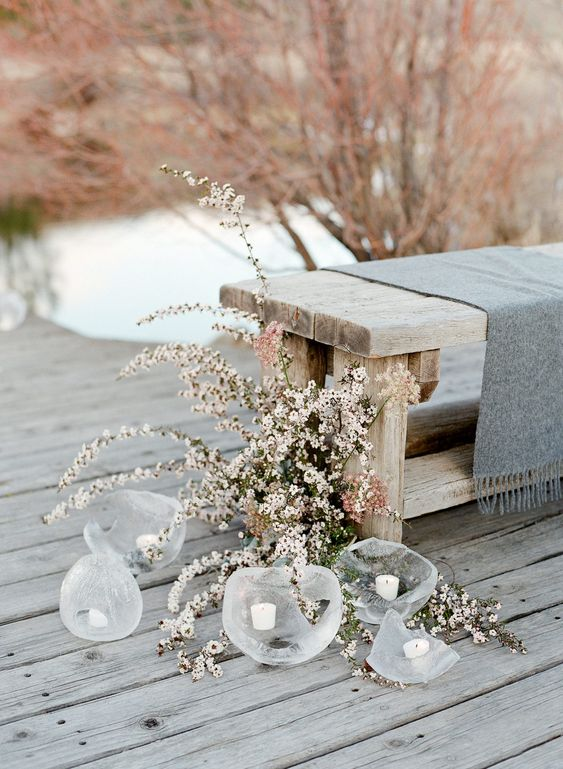 a grey winter wedding ceremony space with wooden benches, grey textiles, blush blooms and candles in glass