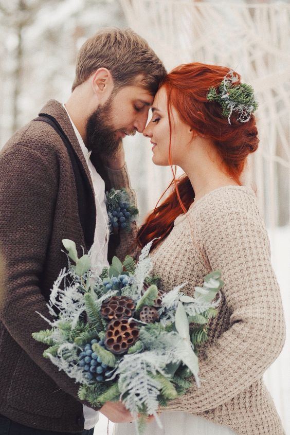 a groom wearing a brown crochet cardigan, a bride wearing a tan knit cardigan and greenery in her hair