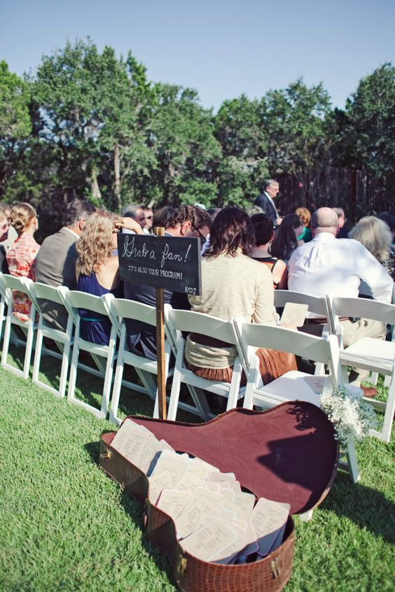 a guitar case used for serving wedding programs is a lovely rustic idea, simple and cute