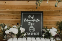 a hot chocolate bar with greenery, white blooms and a chalkboard sign is a cool idea for a rustic winter wedding