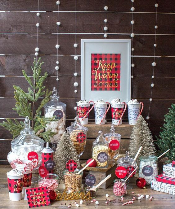 a hot cocoa bar with red plaid touches, snowball garlands, letters, sweets and candies in matching jars