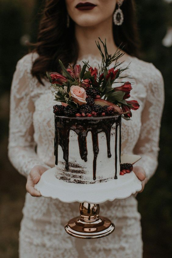 a mini wedding cake with chocolate drip, blackberries, pomegranate seeds, greenery, blush and red blooms
