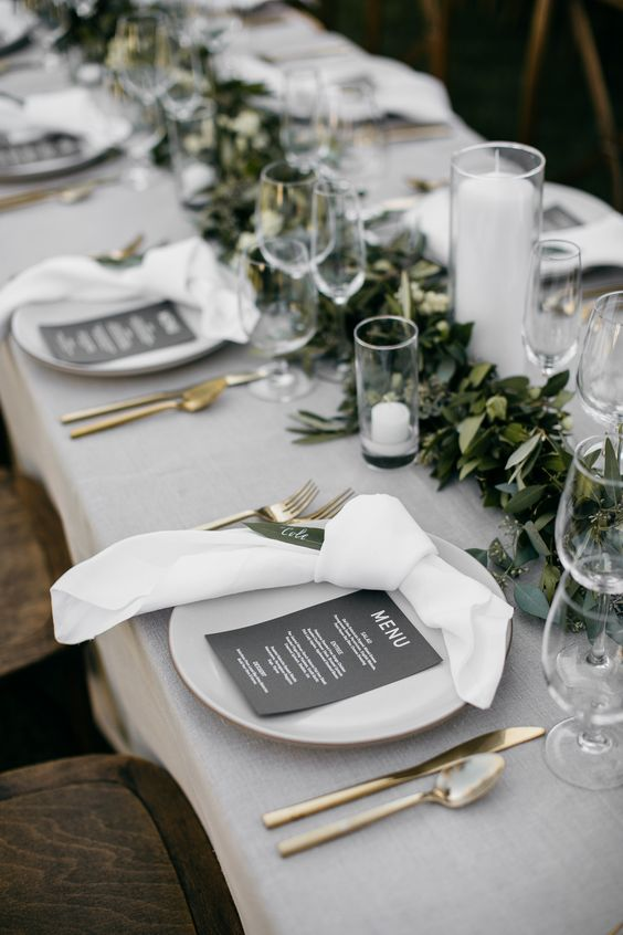 a modern refined wedding tablescape with green and white linens, a greenery runner, candles, gold cutlery is amazing
