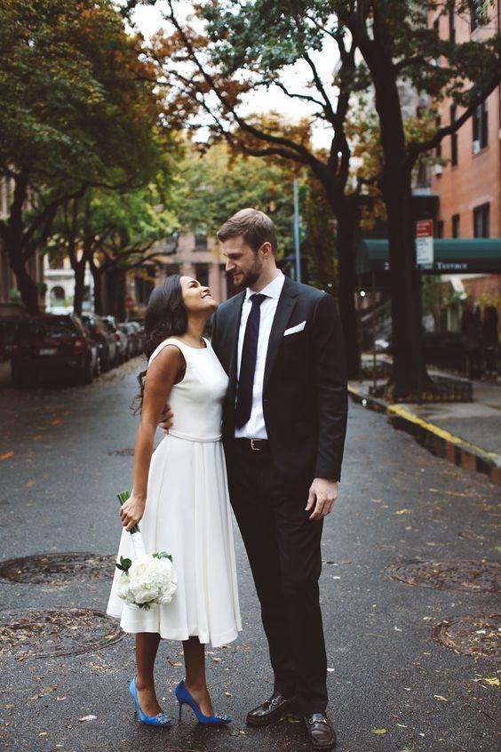 a modern sleeveless midi wedding dress with a plain bodice, a pleated midi skirt and blue shoes is elegant