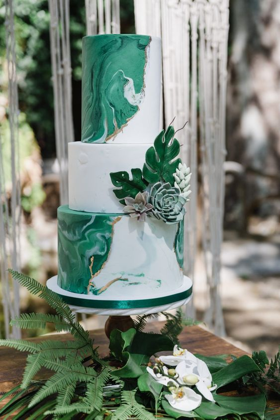 a modern tropical wedding cake with white marble and green marble tiers and sugar leaves and succulents is a very chic and cool idea