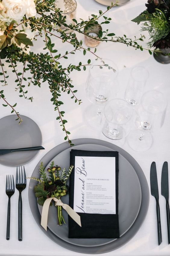 a modern wedding tablescape with greenery, candles, matte grey plates, a black napkin and greenery
