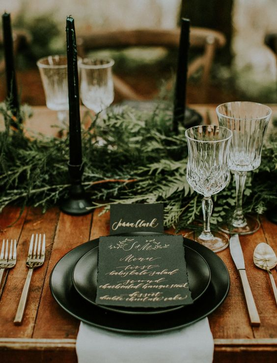 a moody winter wedding tablescape with an evergreen runner, black candles, black plates and an elegant black and copper paper goods