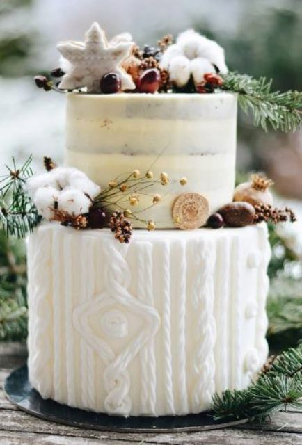 a naked and frosted wedding cake with a sweater pattern, cotton, berries, nuts, cookies and fir