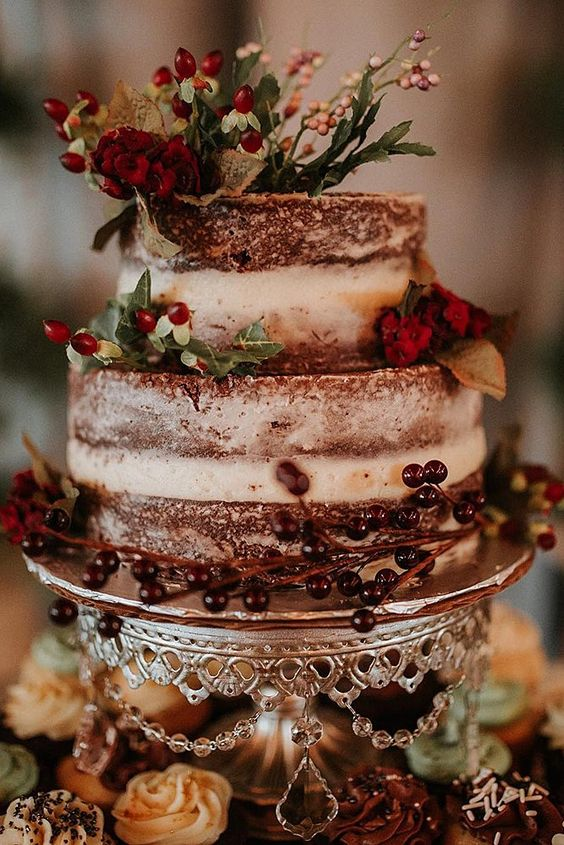 a naked chocolate wedding cake with berries, red blooms and greenery for a rustic winter wedding