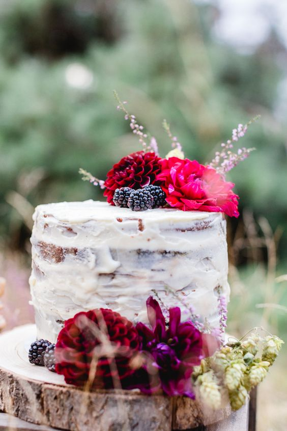 a naked wedding cake topped with berries and bright blooms will easily fit a fall or winter wedding