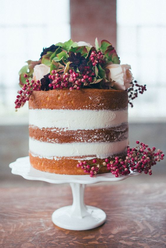 a naked wedding cake topped with berries, white and deep purple blooms and greenery will fit a fall or winter wedding