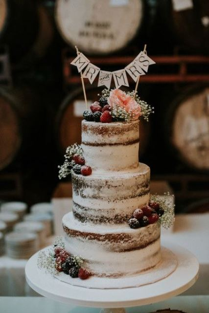 a naked wedding cake topped with blooms, sugared berries, banners for a rustic wedding