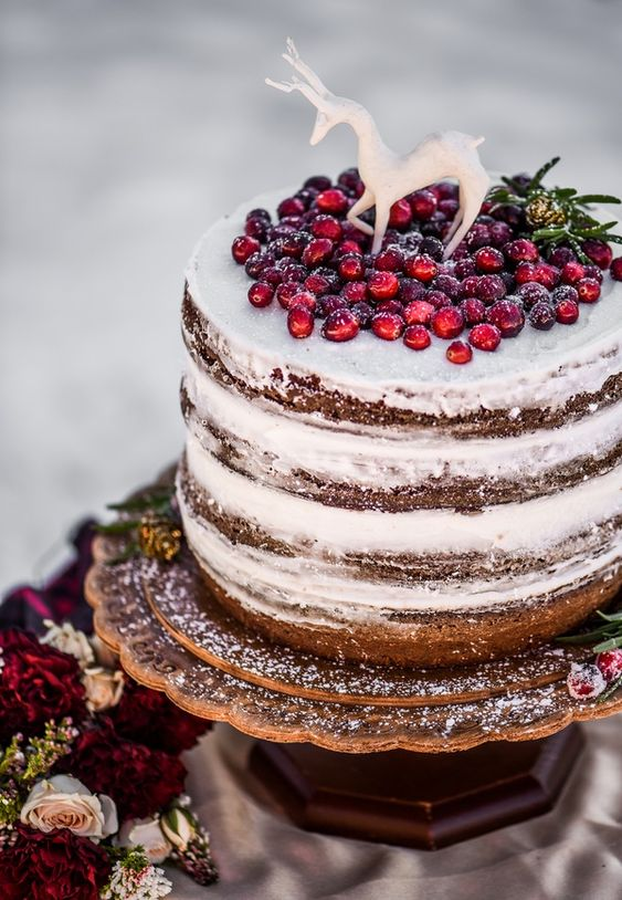 a naked wedding cake topped with cranberries and a sugar deer is a lovely idea for a woodland winter wedding