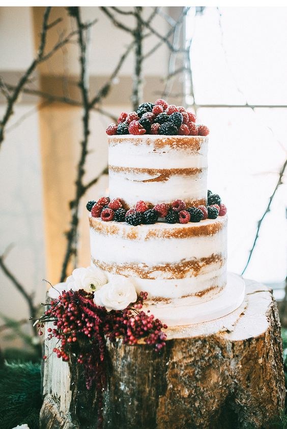 a naked wedding cake topped with fresh berries and white blooms is a stylish idea for many weddings