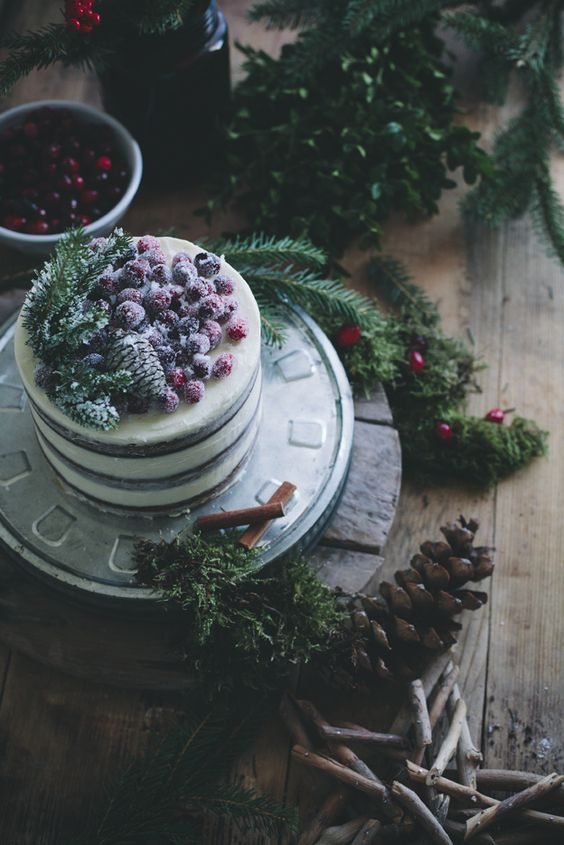 a naked wedding cake topped with pinecones, fir branches and sugared berries is a stylish idea for a Christmas wedding