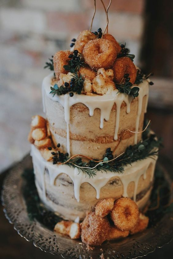 a naked wedding cake with dripping, evergreens, privet berries and topped with donuts