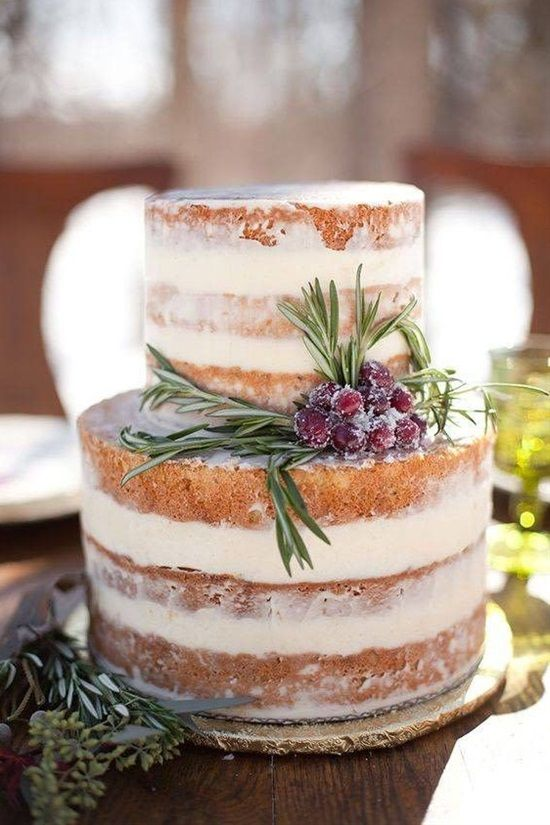 a naked wedding cake with evergreens and sugared cranberries for a rustic winter wedding