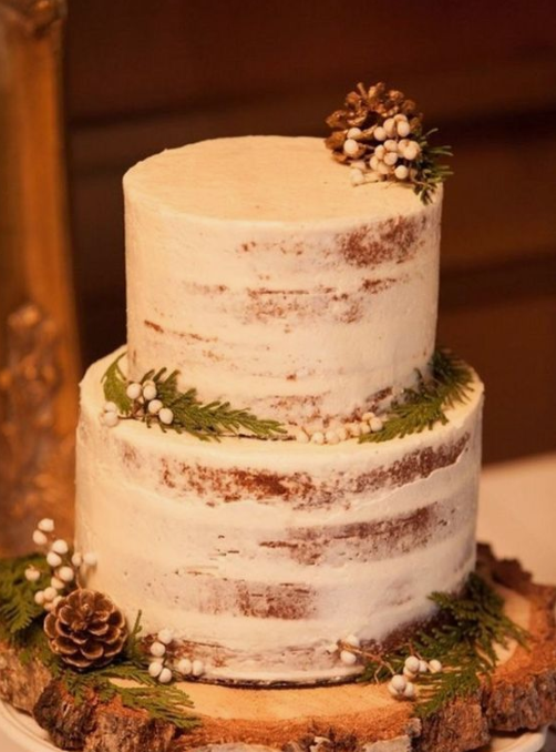 a naked wedding cake with evergreens, berries and pinecones on a wood slice for a rustic winter wedding
