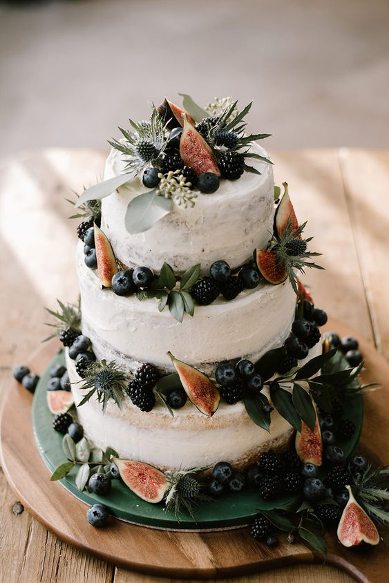 a naked wedding cake with figs, blackberries, blueberries, greenery and thistles for a boho winter wedding