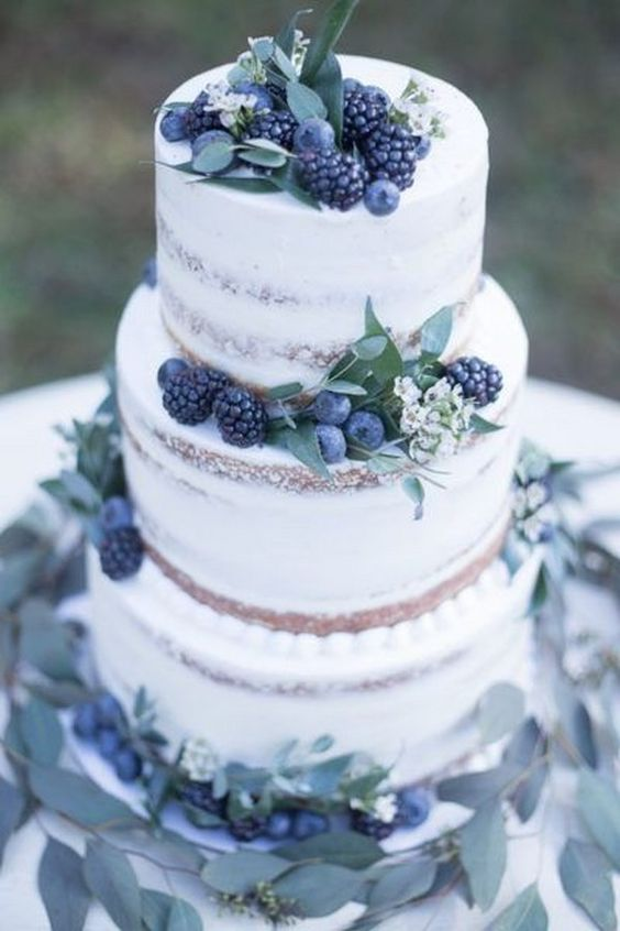 a naked wedding cake with greenery, white blooms and fresh berries for a pale winter wedding