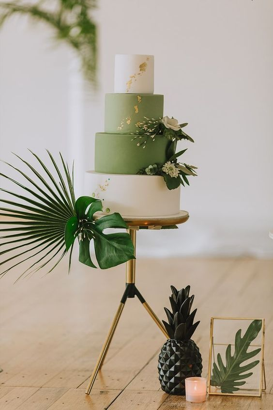 a pretty tropical wedding cale with white and green tiers, white blooms and gold leaf is a cool idea for a modern tropical wedding