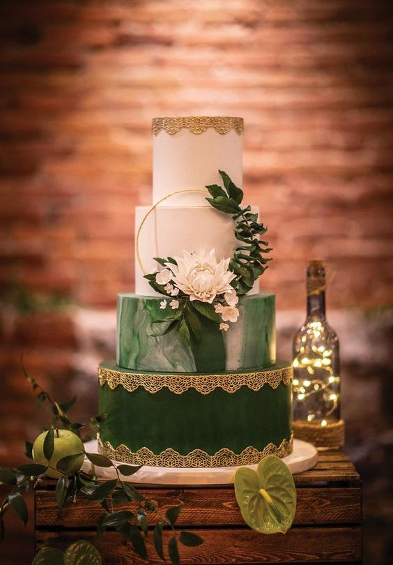 a refined vintage white and green wedding cake with a marble and gold lace tier, with white blooms and greenery