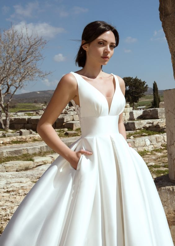 a refined wedding ballgown with thick straps and a deep neckline, a pleated full skirt with pockets is a non-typical solution