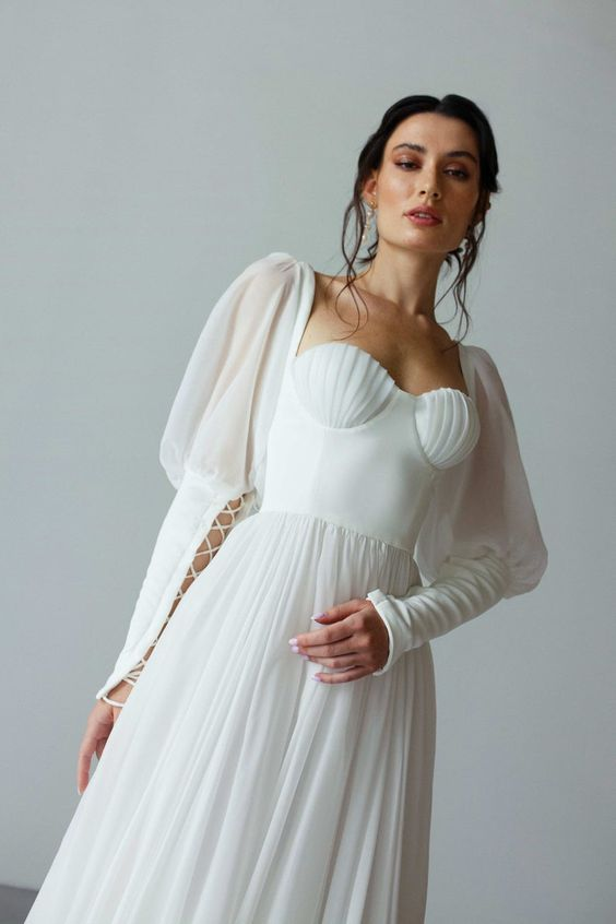a refined wedding gown with a pleated skirt, a plain and seashell-like bodice, puff and lace up sleeves is dramatic