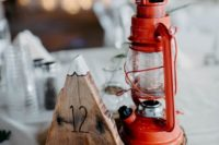 a rustic and camp winter wedding centerpiece of a wood slice, a mountain of wood and a lantern is great