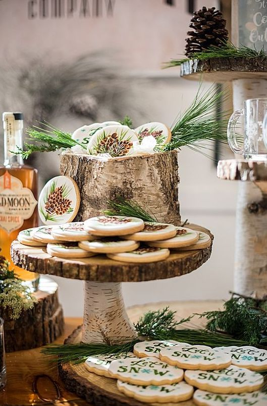 a rustic sweets bar with birch stumps and branch stands and wood slice trays and holders for food and drinks