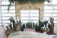 a rustic wedding ceremony backdrop of a faux mantel, greenery, antlers, tree stumps with candles and antlers and a fur rug