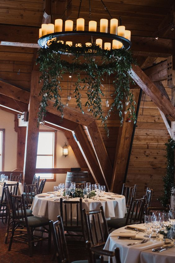 a rustic wedding reception space with a greenery and candle chandelier, evergreens on the tables and wood clad walls