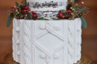 a rustic winter wedding cake with a naked and a sweater-inspired tier, berries and greenery on a glam metallic stand