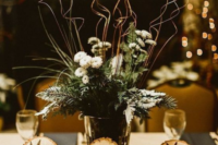 a rustic winter wedding centerpiece of evergreens, tree stumps, a vase with evergreens, blooms and twigs for a rustic winter wedding