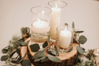 a rustic winter wedding centerpiece of wood slices, greenery and candles in candleholders