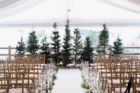 a rustic winter wedding ceremony space with a Christmas tree backdrop, candles in jars and greenery