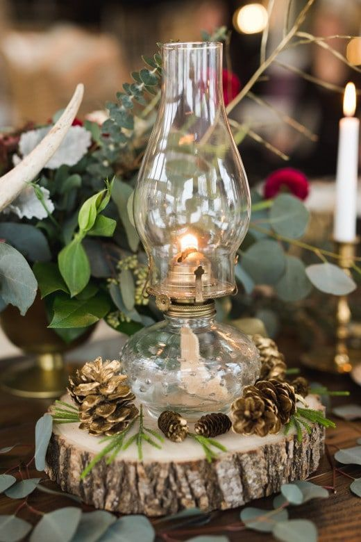 a rustic winter wedding decoration of a wood slice, a lantern and gilded pinecones plus greenery around