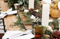 a rustic winter wedding table with an evergreen and pinecone runner, lush white blooms, pillar candles and an uncovered table