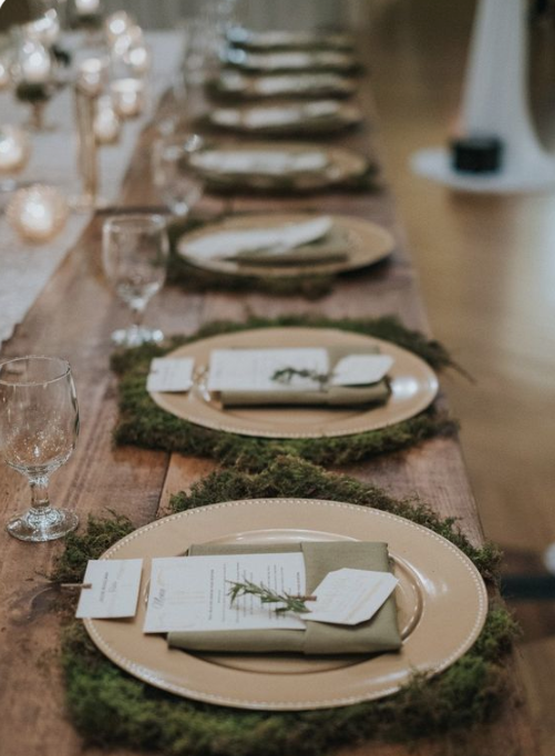a rustic winter wedding tablescape with moss, gold chargers, evergreens and neutral napkins looks very cozy and very intimate