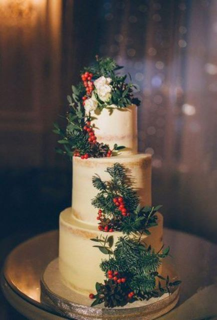 a semi-frosted wedding cake decorated with berries, greenery, pinecones and white blooms for winter