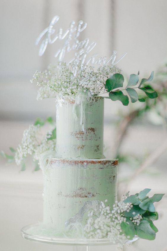 a semi-naked green wedding cake topped with white baby's breath, eucalyptus and an acrylic topper for a modern boho wedding