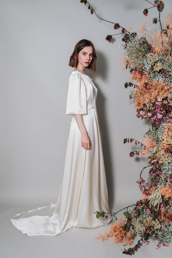 a silk wedding dress with short sleeves, a high neckline and slight pleating on the skirt plus a train is gorgeous