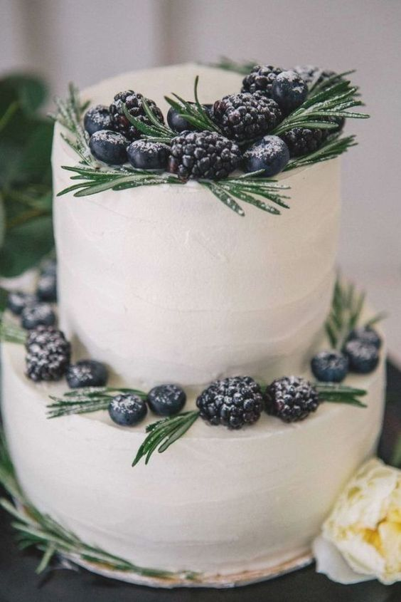 a simple white buttercream wedding cake decorated with rosemary and fresh berries is a stylish idea for a winter wedding