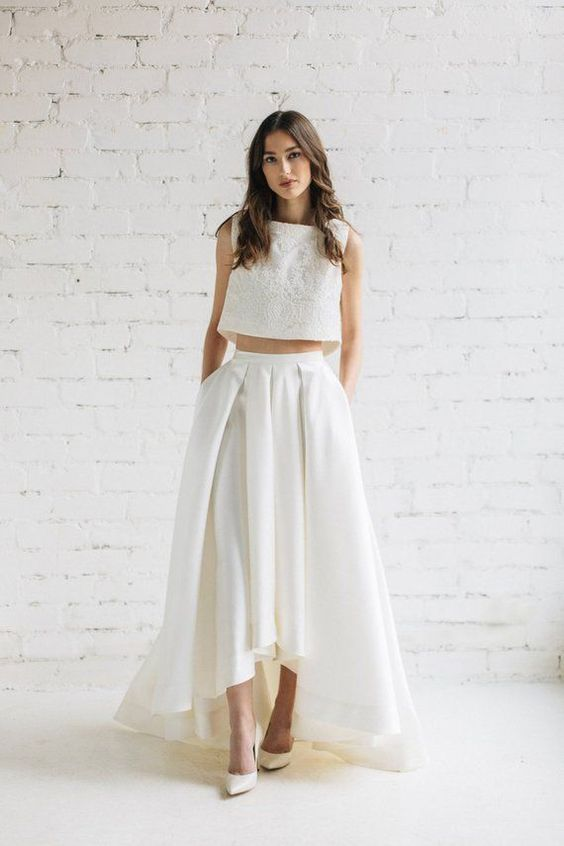 a sleeveless crop top of lace and a pleated high low maxi skirt for a trendy and stylish bridal look