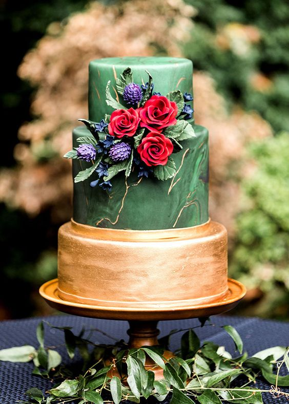 a statement green marble and gold wedding cake with fresh and sugar blooms of jewel tones and foliage