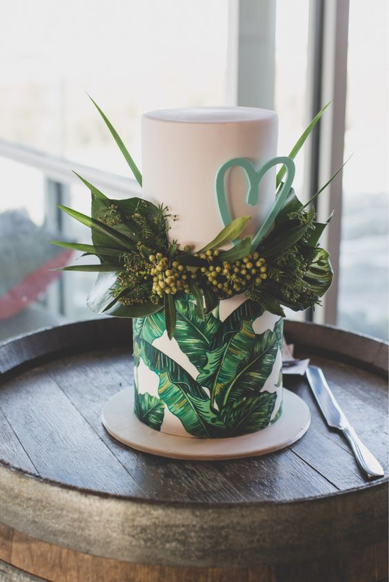 a terrific tropical wedding cake with banana leaves painted, fresh foliage and a green sugar heart for a modern tropical wedding